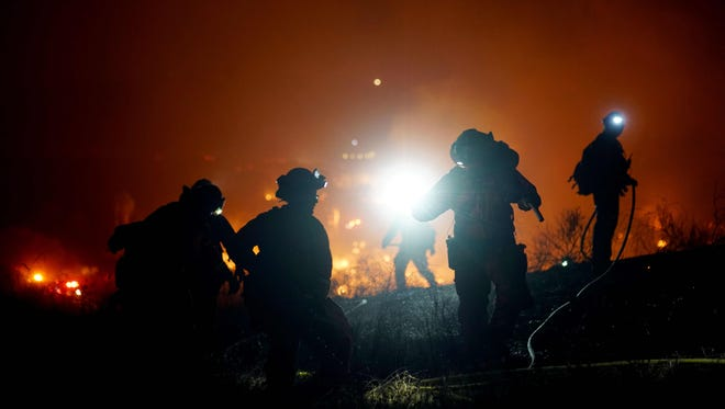 Firefighters battle the Lilac fire in Bonsall, California on Dec. 7.