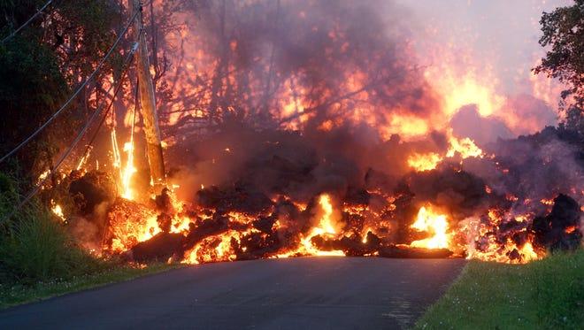 Lava pours down a road in the Leilani Estates neighborhood on May 6, 2018 near Pahoa, Hawaii.