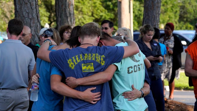 People comfort each other at a vigil set up close to Santa Fe High School where a gunman, reported to be a student, shot numerous people in Santa Fe, Texas, May 18, 2018. Ten people are confirmed to have been killed in the shooting and another 10 injured, according to local officials.
