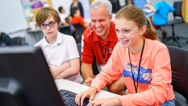 Rose-Hulman Institute of Technology professor David Fisher (center) works with students at Connecting with Code, a summer computing camp Fisher helps organize for elementary and middle school students.