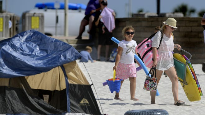 Visitors bring tents and beach toys Saturday to Pensacola Beach. Officials at Pensacola Beach are preparing for huge crowds during the Memorial Day weekend.