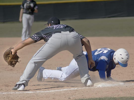 Diving back to first base is Salem's Erich Payne, while Plymouth's Brendan Lacorato stretches for the ball.
