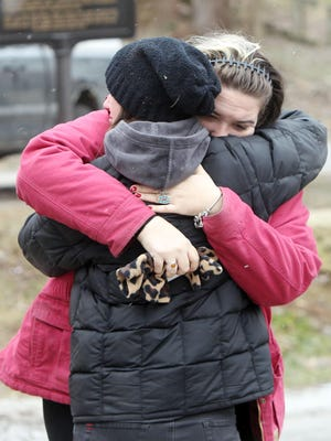 Elizabeth Licis, right, and Ruby Young, both of Rabbit Hash, hug outside the town's 184-year-old general store that was heavily damaged by fire late on Saturday, Feb. 13.