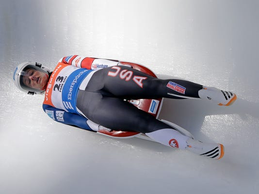 FILE- In this Dec. 17, 2016, file photo, Emily Sweeney, of the United States, slides down the course during a women's World Cup Luge event in Park City, Utah. For whatever reason, sliding sports have always gotten tons of attention from the military, and the team that is wearing red, white and blue in Korea has plenty of people who wear the flag at work as well. Sweeney is in the Army.  (AP Photo/Rick Bowmer, File)