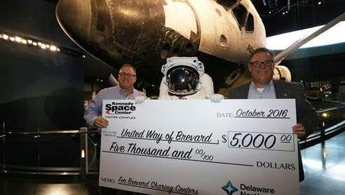 Therrin Protze, chief operating officer of the Kennedy Space Center Visitor Complex, presents Dave Brubaker, president and chief operating officer of Sharing Center of Central Brevard, with a $5,000 check to help those affected by Hurricane Matthew.