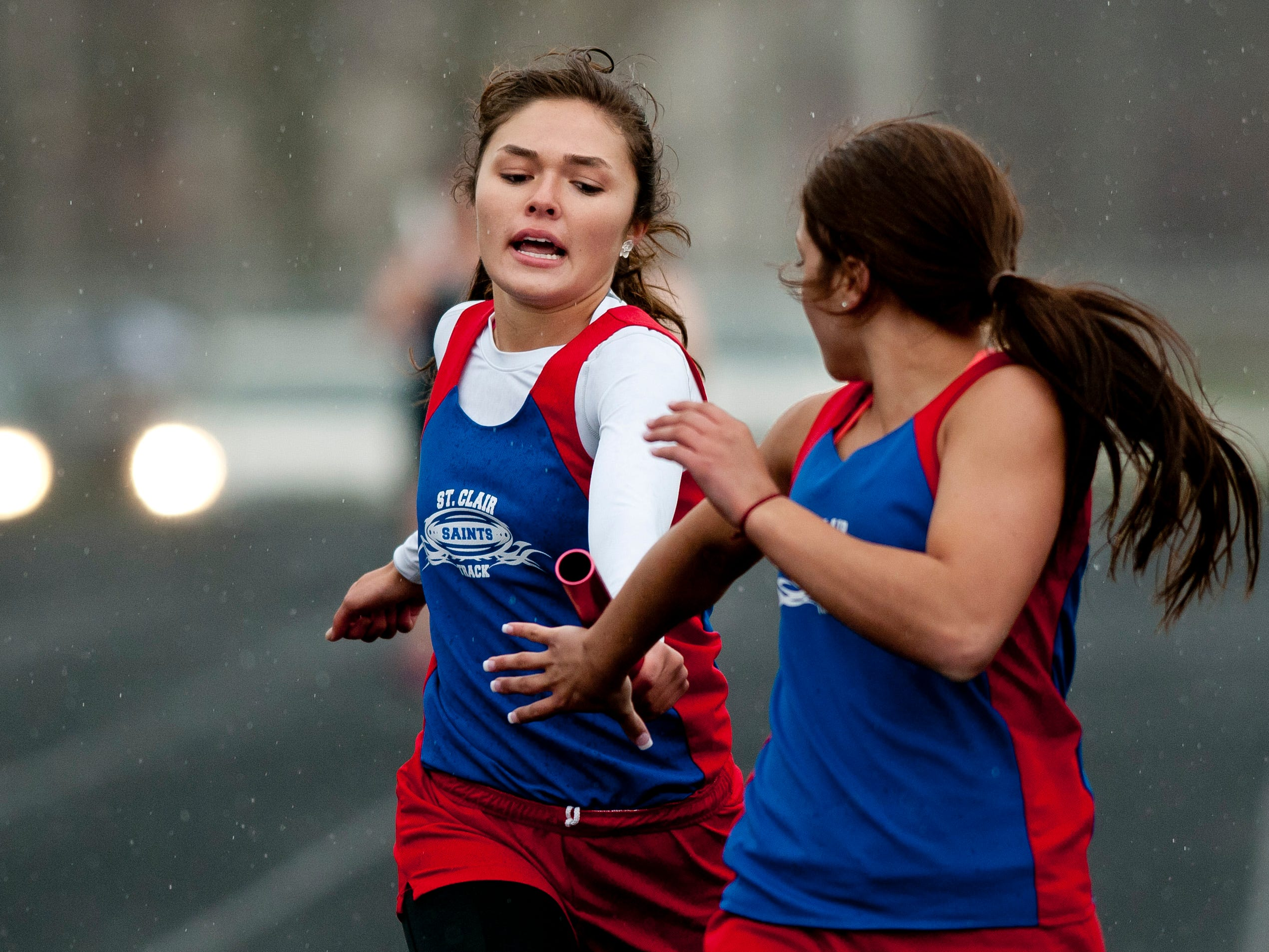 St. Clair junior Kaitlyn McLeod hands off the baton to junior Sam Jozwiak in the 4x200-meter relay during a track meet Thursday, April 30, 2015 at Marysville High School.