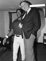 Yankees owner George Steinbrenner hops atop a table in manager Clyde King's office to gain a height advantage over his outfielder Dave Winfield before the team's game with the Milwaukee Brewers in 1982.