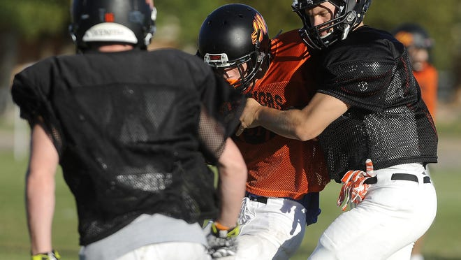 Jack Bren and Jack Schelhaas tackle Chad Zimmer during Washington High School football practice in Sioux Falls, S.D. Monday, August 24, 2015.