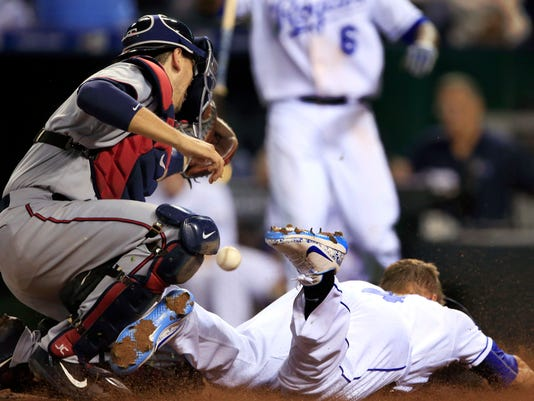 Kansas City Royals' Alex Gordon (4) slides across home plate as the ball gets away from Minnesota Twins catcher Jason Castro, left, during the fifth inning of a baseball game at Kauffman Stadium in Kansas City, Mo., Thursday, Sept. 7, 2017. Gordon was safe on the play. (AP Photo/Orlin Wagner)
