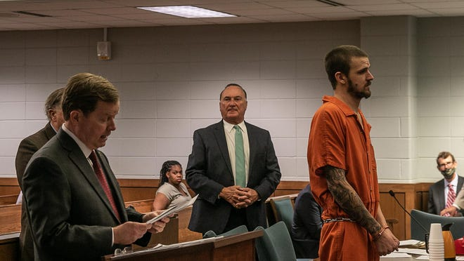 Michael Norris stands before Judge Walter Mills as District Attorneys (at left) reads the charges against him of murdering his grandparents.