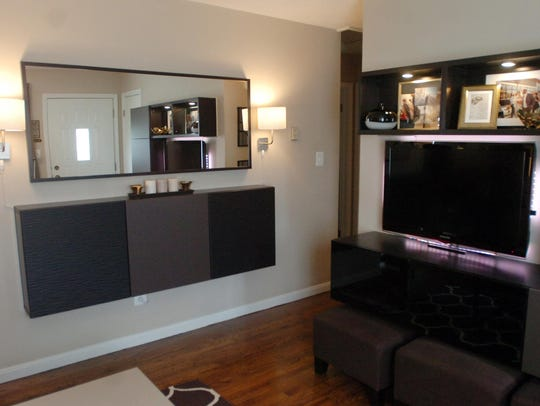 Wall-mounted cabinets and an entertainment center provide