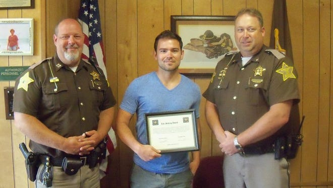 Ryan Schuck (center) recently was given a livesaving award from the Union County Sheriff's Office.