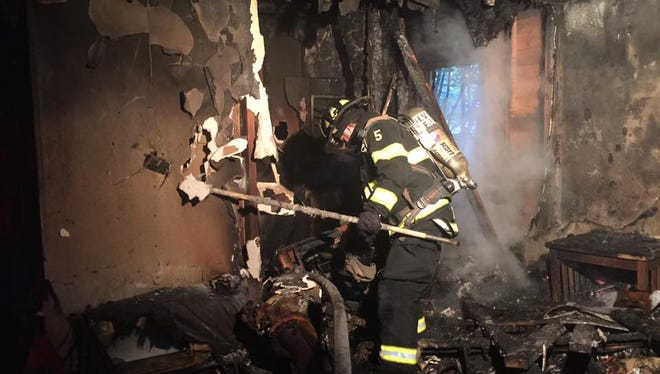 A firefighter works at the scene of a fatal fire on Monday, Oct. 24, 2016.