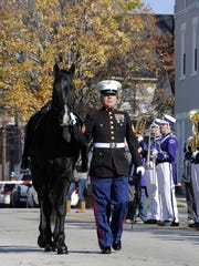 Sgt. Michael Sanchez, of the U.S. Marine Corps, walks with a horse to symbolize the servicemen and women who died in combat during a Veterans Day ceremony in November 2015. Fremont will hold a parade to honor veterans Nov. 12 at 9 a.m. on Front Street.