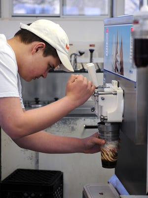 Nick Bossetti, a Danbury High School student, makes a root-beer float for a customer at Netty's Famous Chili Dog stand in Marblehead on Monday night.