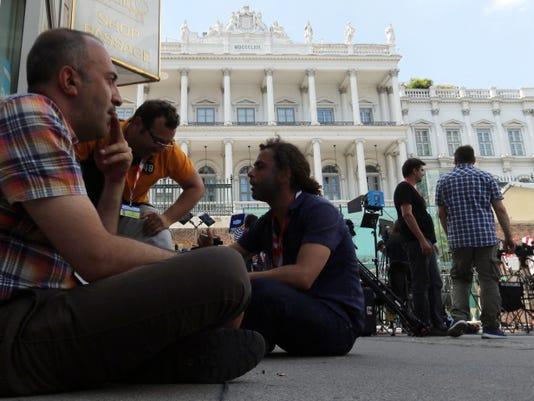 Journalists wait in front of Palais Coburg where closed-door nuclear talks with Iran take place in Vienna, Austria, Wednesday, July 1, 2015. (AP Photo/Ronald Zak)