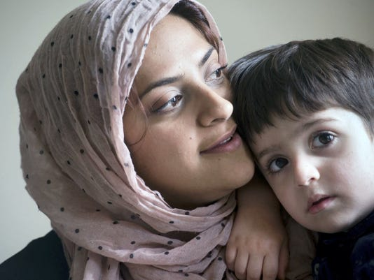 Durre Sharif, left, holds her 3-year-old son, Zain, at their home in Newberry Township. Sharif, originally from London, said York County has been very welcoming to her family overall, and the 'Death to Islam' sign at a West York bar represents the sentiment of a small minority.