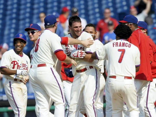 Philadelphia's Jeff Francoeur, middle, celebrates with teammates after hitting a home run in the ninth inning of Sunday's game. Francoeur's two-run homer lifted the Phillies to an 8-7 win against Miami.
