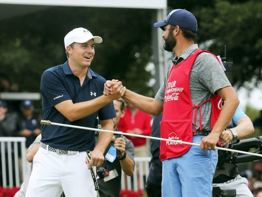 Jordan Speith, left, celebrates with his caddie Sunday after winning the Tour Championship golf tournament the Fed Ex Cup at East Lake Golf Club in Atlanta.
