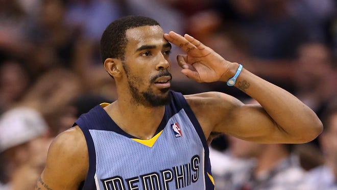 Mike Conley #11 of the Memphis Grizzlies salutes his bench after hitting a three point shot against the Phoenix Suns during the second half of the NBA game at US Airways Center on April 14, 2014 in Phoenix, Arizona.