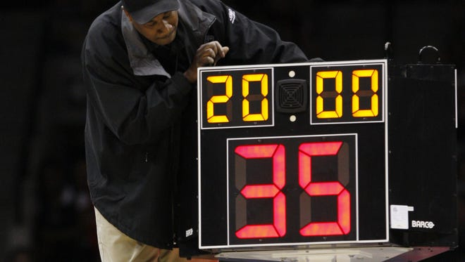 A technician adjusts the shot clock at an NCAA basketball game.