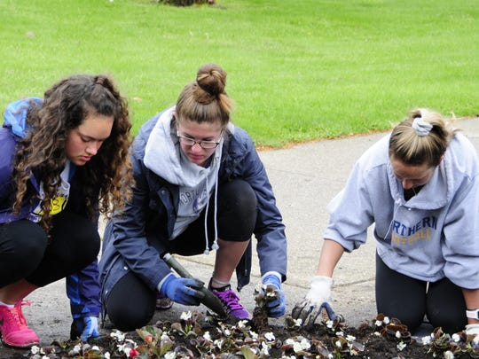 Port Huron Northern Quota Club students Isabella Murray, Katie Touma and Andrea Hartman plant flowers Saturday, May 19, 2018 during Plant Day at Pine Grove Park.