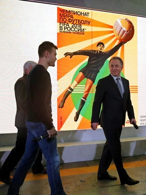 Russian goalkeeper Igor Akinfeev (left) and Russian Deputy Prime Minister Vitaly Mutko walk past the official poster of the 2018 World Cup in Russia during its presentation.