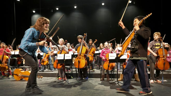 Mark Wood, former member of the Trans-Siberian Orchestra, and Eric Lee, right, rehearse Feb. 17 with Menasha middle school orchestra students at Pickard Auditorium in Neenah. Wood, along with middle and high school students, gave a performance Feb. 18 at Pickard.