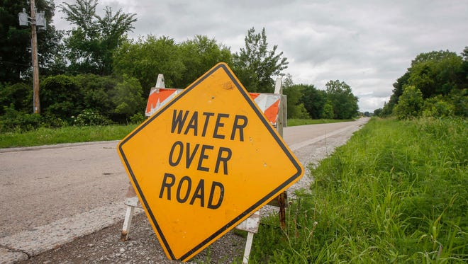 A sign warns motorists along Park Street in Perry on Thursday, June 21, 2018, after a storm dropped heavy rain and produced a tornado north of town on Wednesday.