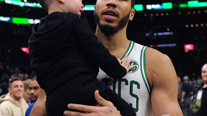 Celtics forward Jayson Tatum holds his son, Deuce, after a game in November at TD Garden. Tatum says he was particularly affected by the death of Michael Brown in Ferguson, Mo., in 2014 because he was a student at a nearby St. Louis high school at the time.