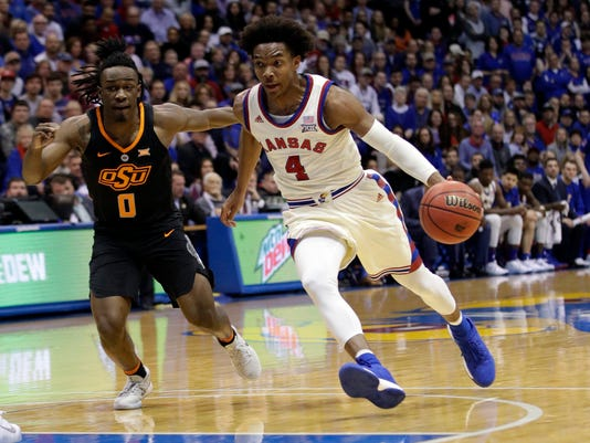 FILE - In this Feb. 3, 2018, file photo, Kansas guard Devonte Graham (4) drives past Oklahoma State guard Brandon Averette (0) during the first half of an NCAA college basketball game in Lawrence, Kan. Graham wanted a team to call his own at Kansas, and didn't want to be responsible for the end of a Big 12 regular-season championship streak that now covers all but the first of coach Bill Self's 15 seasons. The senior guard accomplished both, despite some doubts along the way. Now Graham will try to get the sixth-ranked Jayhawks to the Final Four after predecessor Frank Mason III came up a game short the past two years. (AP Photo/Orlin Wagner, File)
