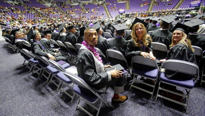 Portland Trail Blazers point guard Damian Lillard, center, looks on during commencement exercises at Weber State Friday, May 1, 2015, in Ogden, Utah. Lillard graduated with a degree in professional sales from the College of Applied Science & Technology.