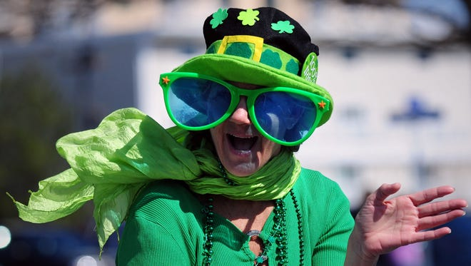 Sherri Caudeloro of Showell waves to the crowd as she marches for Atlantic General Hospital in last year's St. Patrick's Day Parade in Ocean City.