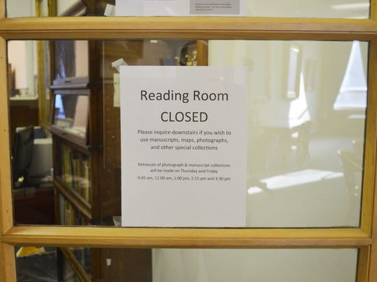 A sign hangs on the door of the reading room on Friday at the State Historical Society of Iowa's Centennial Building. The library's public hours have been cut back to three days a week, and its reading room is open only at limited times.