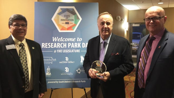 USD President James Abbott, center, was presented the inaugural, 'State of Innovation' Visionary Award by South Dakota's Research Parks. Presenting the award was Dwaine Chapel, executive director, the Research Park at SDSU, on left, and Rich Naser, Jr., president of the USD Discovery District, on the right.