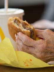 Dorothy Fletcher enjoys a cheeseburger while being interviewed at a McDonald's in Noblesville. She turns 100 on Dec. 23.