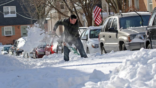 Anthony Moore, a resident of Laurel Street near Delaware Avenue in Trolly Square, tries to dig out his Jeep to got to work Monday morning. The Street still had not been plowed.