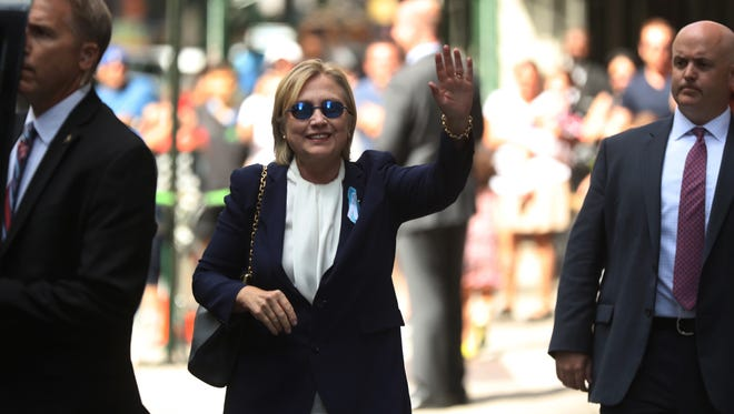 """Democratic presidential candidate Hillary Clinton waves after leaving an apartment building Sunday, Sept. 11, 2016, in New York. Clinton's campaign said the Democratic presidential nominee left the 9/11 anniversary ceremony in New York early after feeling """"overheated."""""""