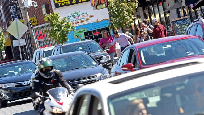 Traffic drives on Main Street in Newark on Thursday. The city is asking developers to pitch a mixed-use development proposal including a parking garage potentially to be built on city property.
