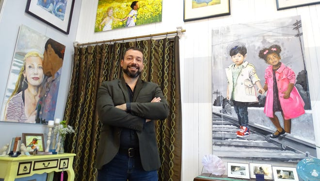 Ivan Pellot stands in front of a few of the paintings he's featuring at Green Room Gallery and Productions downtown Mansfield.