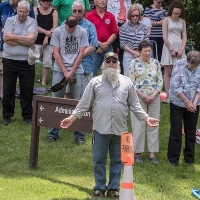 Attendees pray during the Memorial Day event at Fort