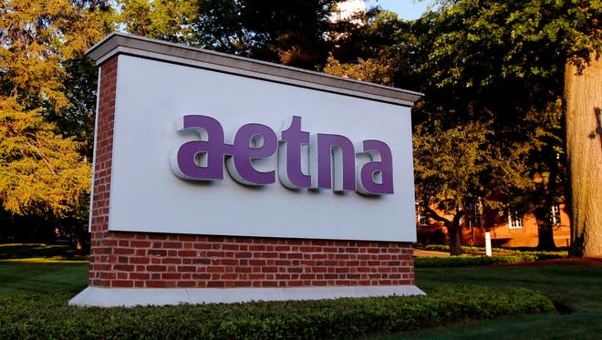 A sign stands on the campus of the Aetna headquarters in Hartford, Conn. Some major health insurers plan to take a little sting out of prescription drug prices by giving customers rebates at the pharmacy counter, and they could spark a trend. Aetna and UnitedHealthcare both say they will begin passing rebates they get from drugmakers along to some of their customers starting next year.
