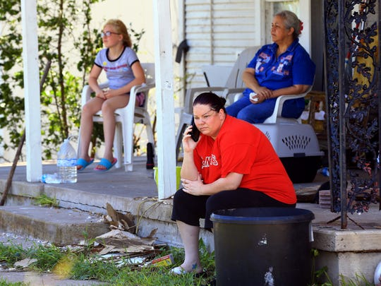 Desiree Nesloney talks on the phone with a friend as Esther Pridgen (back left) and Olga Tanguma (right) sit outside after Hurricane Harvey destroyed their home on Tuesday, Aug. 29, 2017, in Woodsboro, Texas. Harvey struck the Texas Coastal Bend as a Category 4 Friday, August 25, 2017.