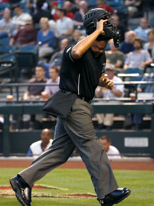 Home plate umpire Kerwin Danley throws off his mask after being hit in the face by a foul ball by Arizona Diamondbacks' Nick Ahmed during the second inning of a baseball game against the Washington Nationals, Tuesday, May 12, 2015, in Phoenix. (AP Photo/Matt York)