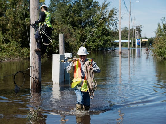 A lineman works to restore power lines near I-95 after the area was flooded by rain from Hurricane Matthew in Lumberton, N.C., Tuesday, Oct. 11, 2016.