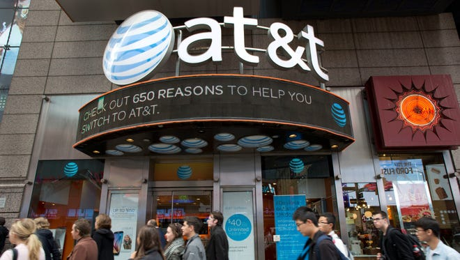 People walk by an AT&T retail store, Monday, Oct. 24, 2016, in New York.