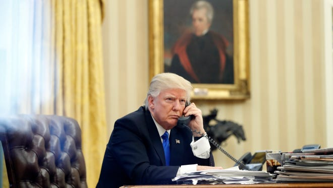 President Donald Trump speaks on the phone in the Oval Office of the White House on Jan. 28, 2017, in Washington. Behind him is a portrait of President Andrew Jackson.