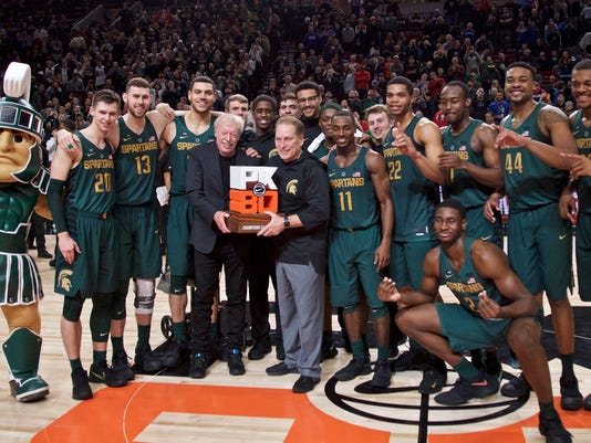Michigan State head coach Tom Izzo and Nike founder Phil Knight, center, hold the PK80 trophy after defeating North Carolina in an NCAA college basketball game in the Phil Knight Invitational tournament in Portland, Ore., Sunday, Nov. 26, 2017. Michigan State won, 63-45. (AP Photo/Craig Mitchelldyer)