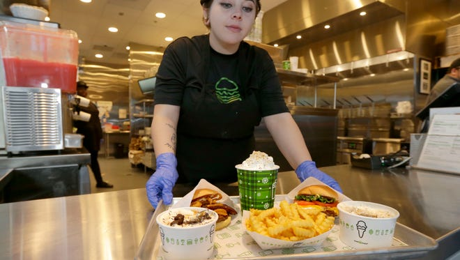 Lilith Westmore, a Shake Shack team member, serves up a tray of items.  - SHAKESHACK - Wisconsin's first Shake Shack restaurant gave a glimpse inside the new restaurant and some of the food items on Tuesday, December 5, 2017.  The burgers, friesand shake joint in the Third Ward at 220 E. Buffalo St., Milwaukee plans to open on Wednesday, December 6. -  Photo by Mike De Sisti / Milwaukee Journal Sentinel