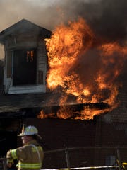 Flames reemerge from a home at 5114 Mesker Park Drive in Evansville Monday afternoon.